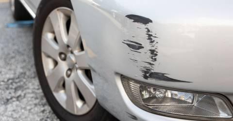 Een grijze auto met wat lichte schade op de voorbumper